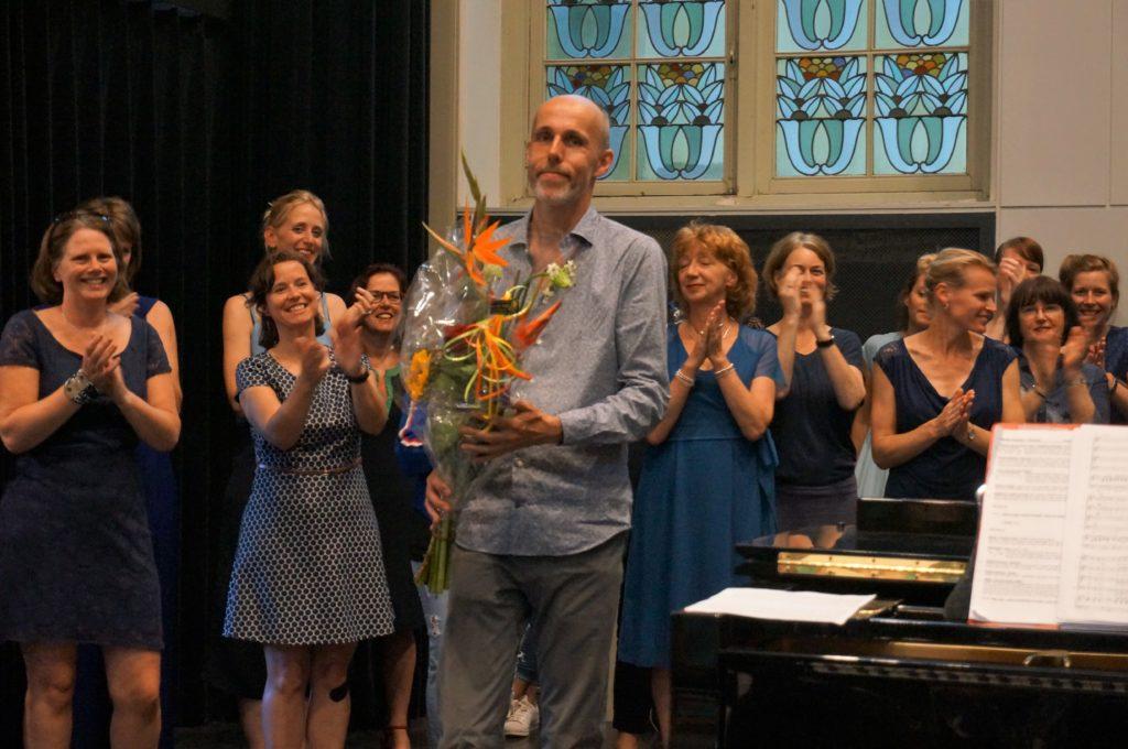 Dirigent Jurriaan Grootes krijgt bloemen aan het einde van het optreden van Popkoor Utrecht.